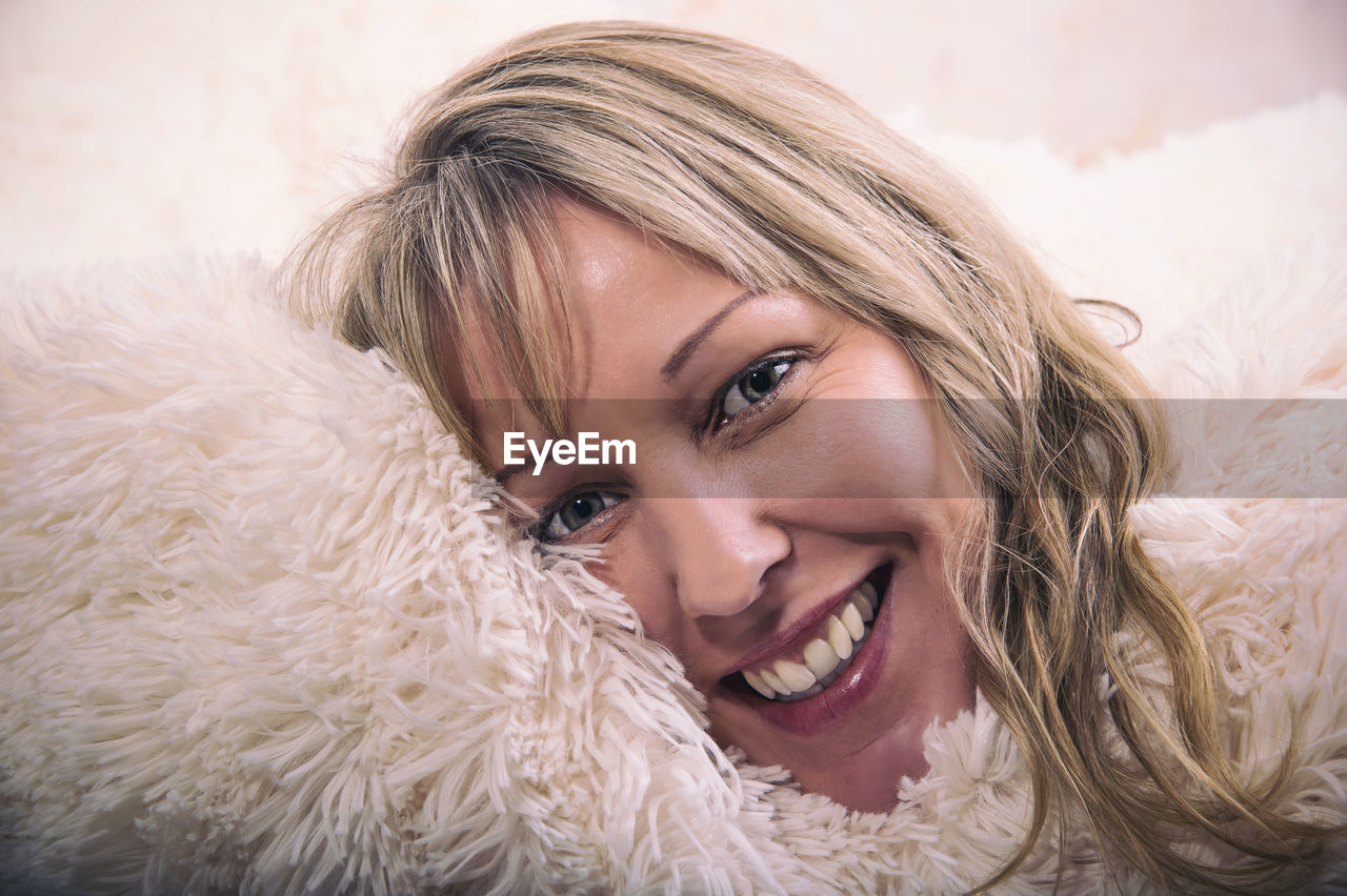 Close-up portrait of smiling mature woman relaxing on fur bed at home
