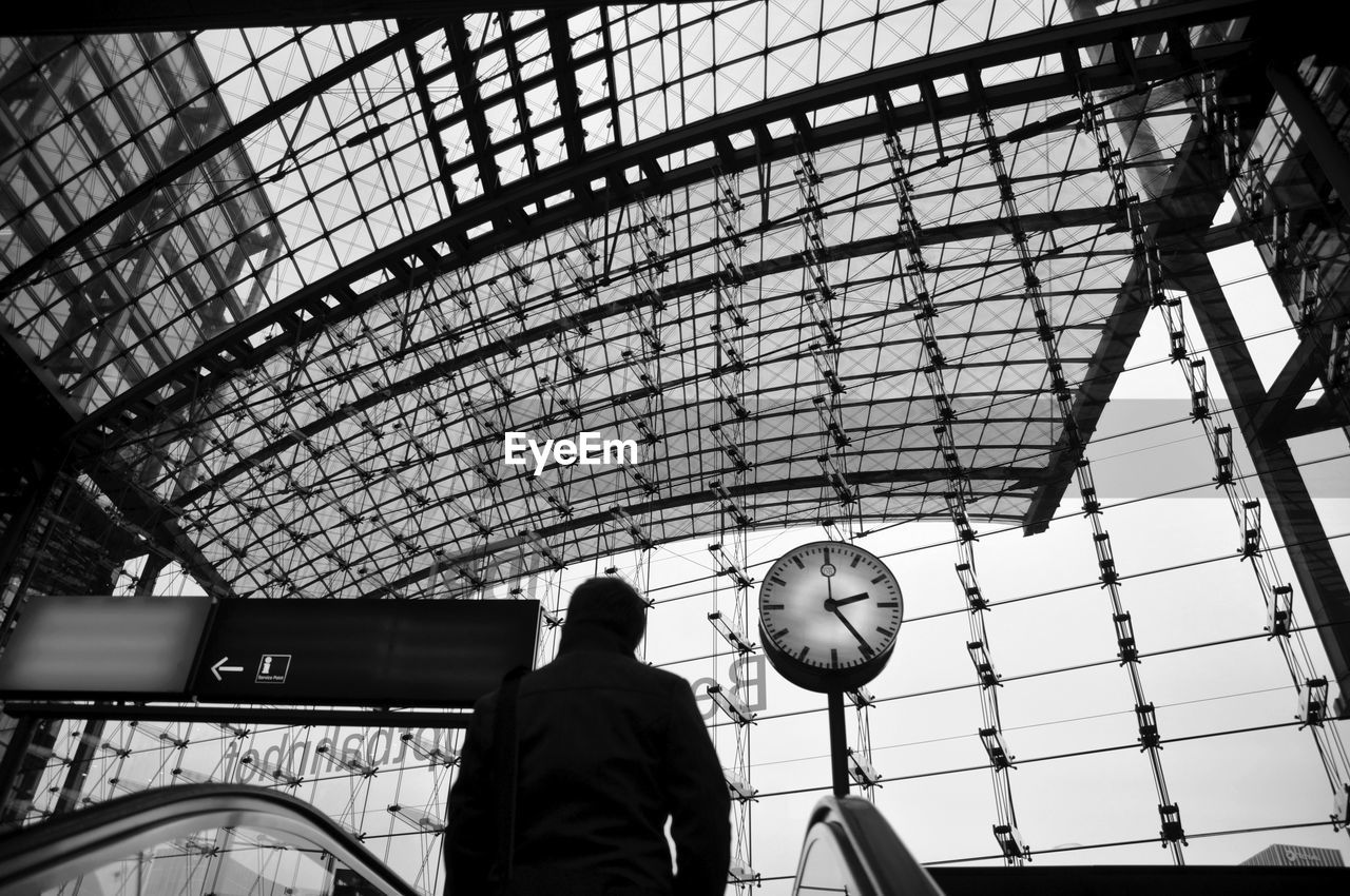 time, clock, indoors, real people, rear view, men, low angle view, railroad station, day, standing, lifestyles, one person, architecture, minute hand, clock face, people