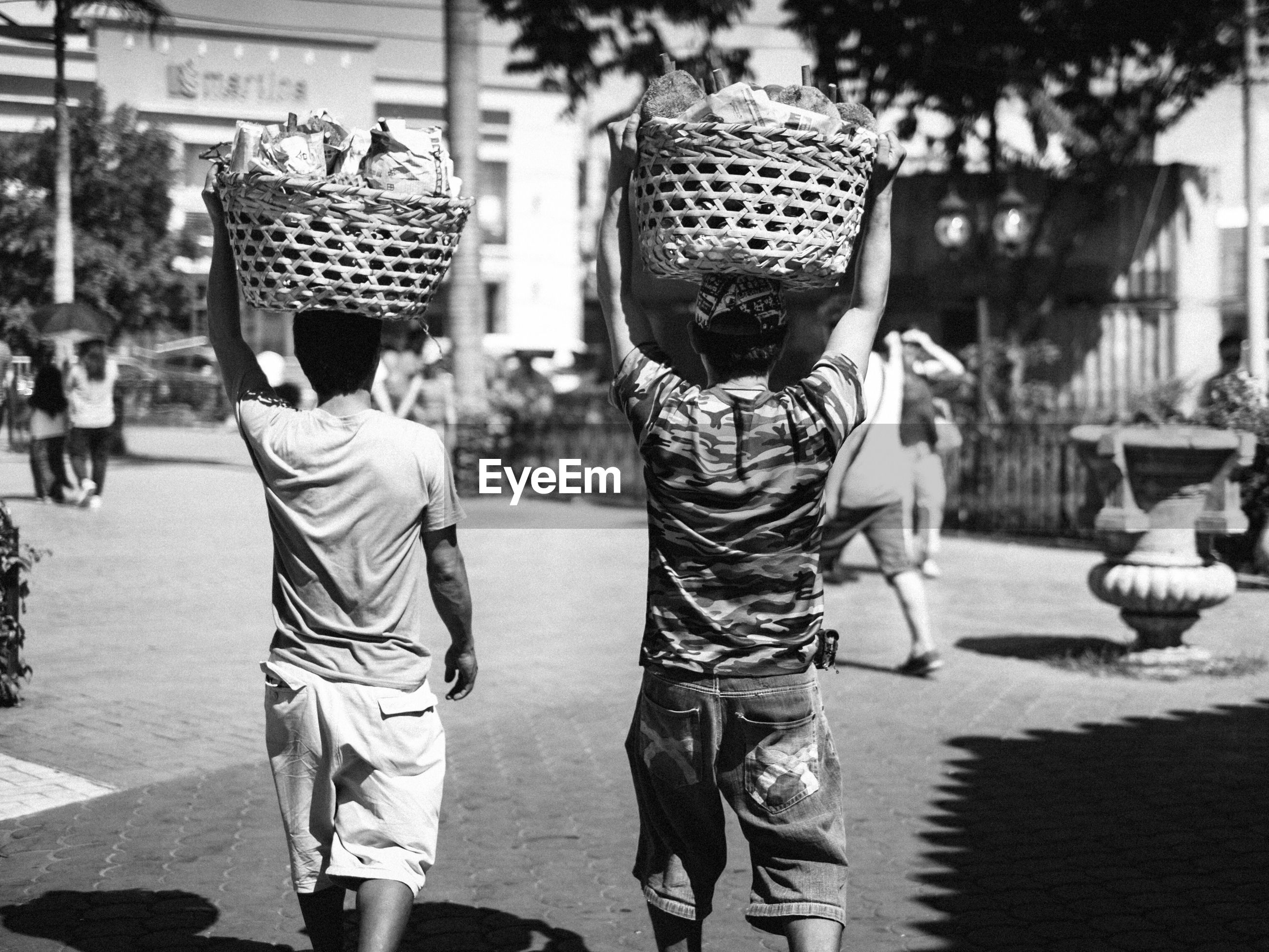 Rear view of men carrying basket while walking on road