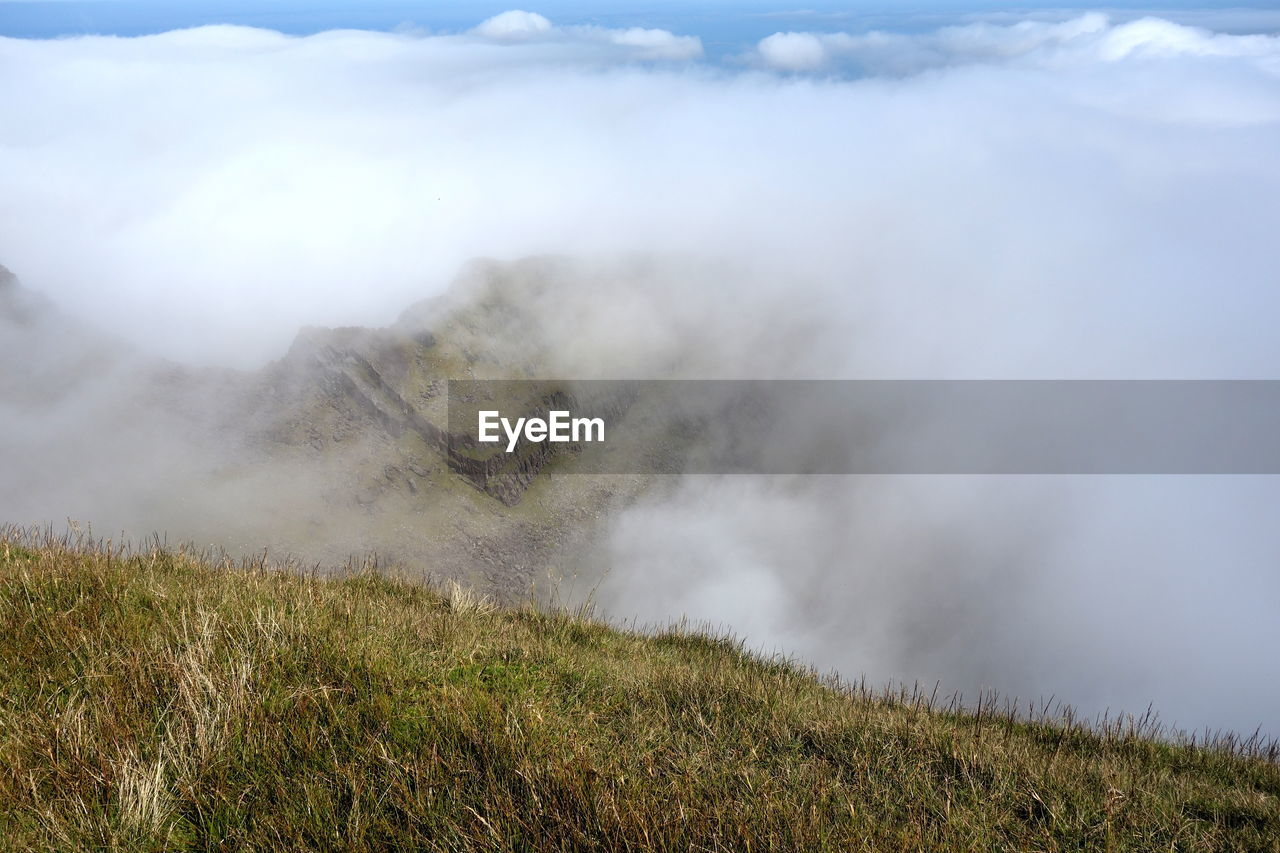 beauty in nature, grass, landscape, non-urban scene, environment, plant, land, scenics - nature, nature, day, no people, cloud - sky, mountain, tranquil scene, tranquility, smoke - physical structure, sky, field, geology, volcano, power in nature