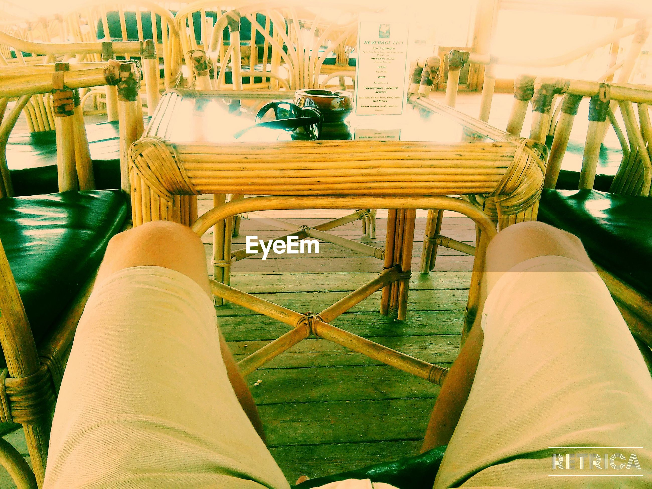 low section, person, relaxation, leisure activity, lifestyles, sitting, chair, personal perspective, wood - material, railing, men, legs crossed at ankle, shoe, day, indoors, built structure