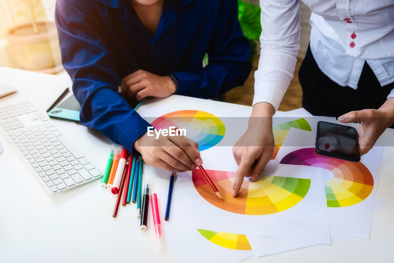 High angle view of design professionals working over color swatches at table