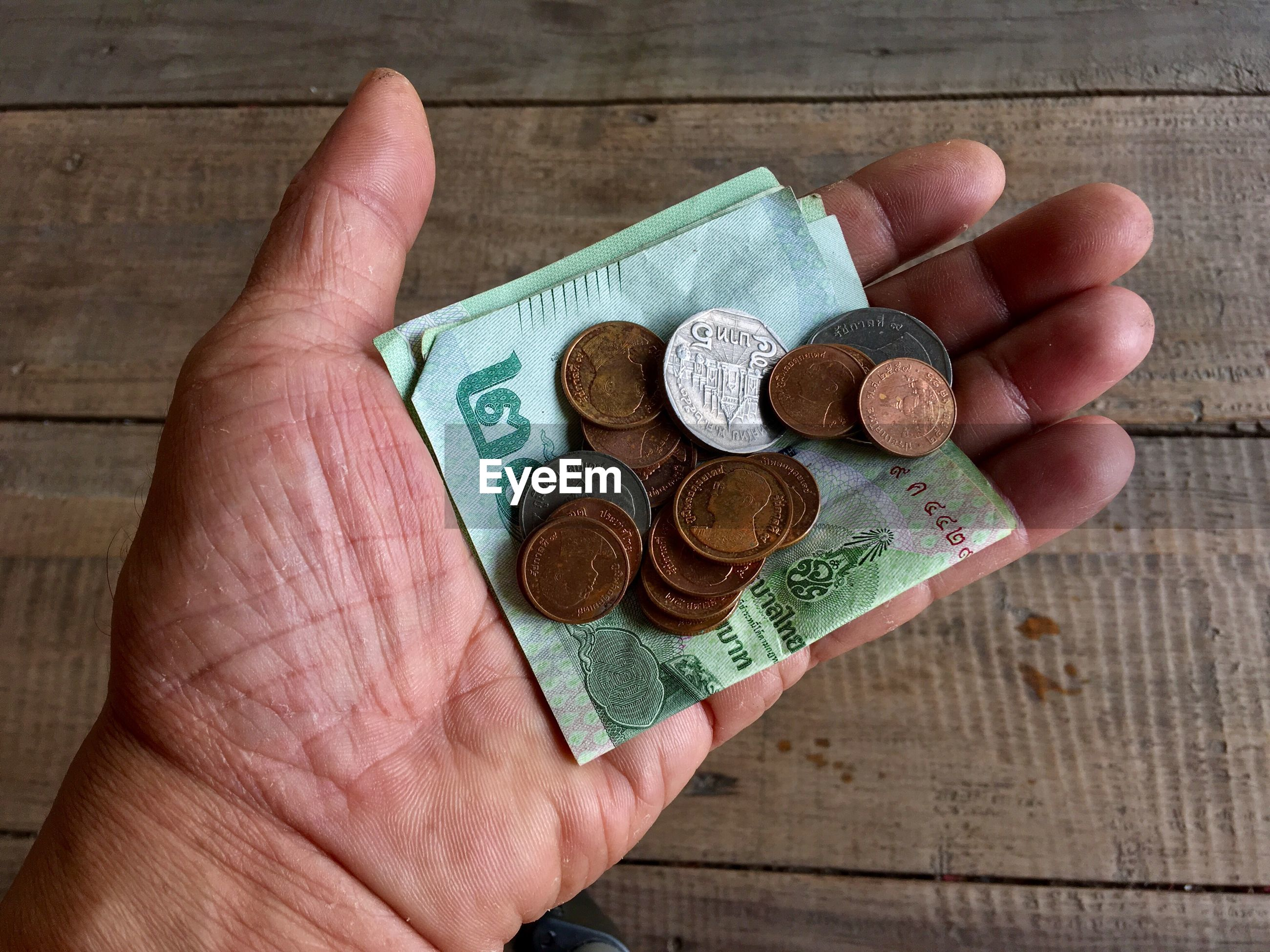 Cropped hand of man holding currency at table