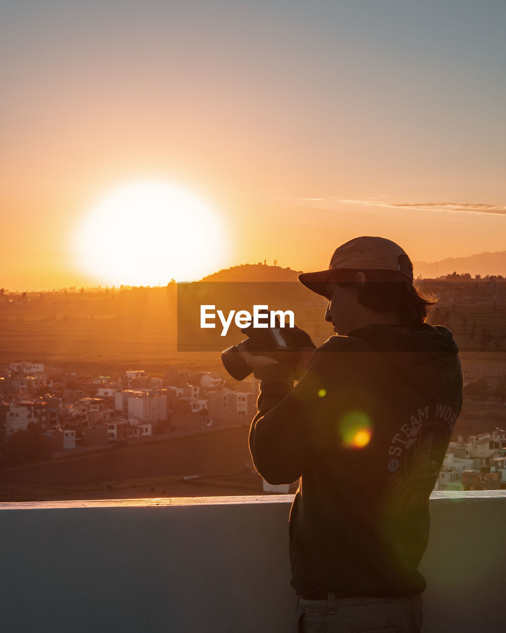 sunset, sky, real people, one person, orange color, sun, photographing, photography themes, nature, lens flare, standing, men, sunlight, building exterior, camera - photographic equipment, technology, activity, wireless technology, architecture, side view, cityscape, outdoors