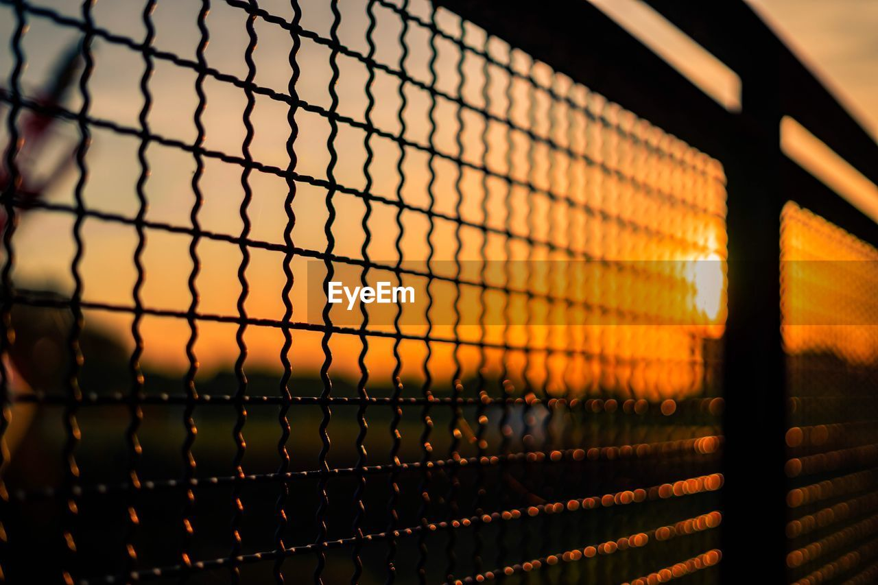 sunset, fence, barrier, metal, boundary, no people, focus on foreground, sky, pattern, chainlink fence, orange color, protection, security, safety, nature, close-up, selective focus, outdoors, grid, sunlight