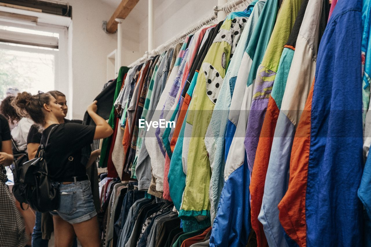 casual clothing, indoors, people, adult, choice, variation, women, clothing, real people, retail, large group of objects, standing, rack, leisure activity, men, lifestyles, multi colored, textile, store, in a row, fashion