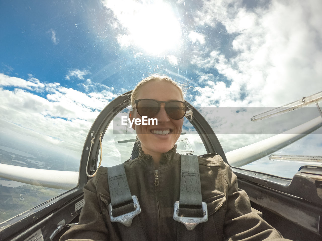 transportation, smiling, glasses, mode of transportation, one person, portrait, sky, cloud - sky, looking at camera, adult, day, front view, women, car, travel, real people, sunglasses, lifestyles, nature, happiness, fashion, outdoors