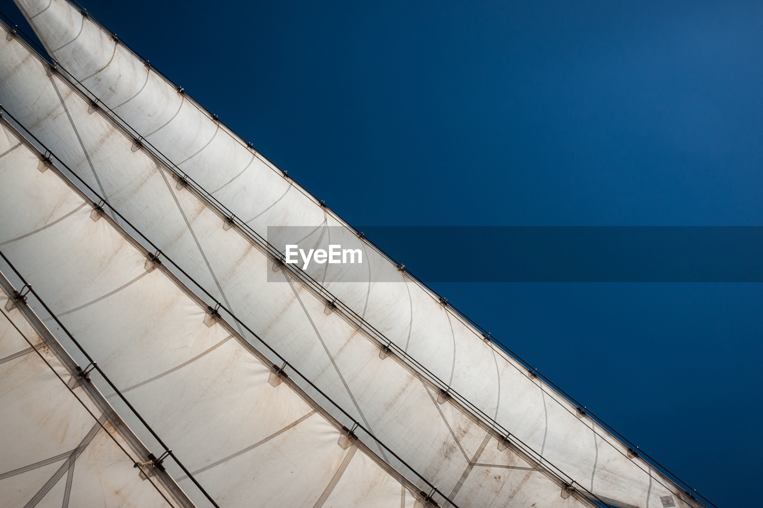 Low angle view of sailboat against clear blue sky