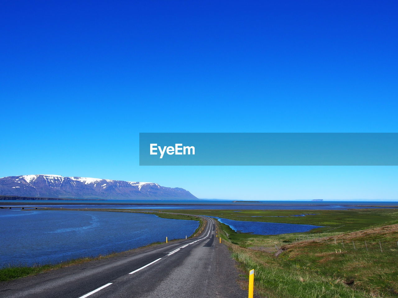 sky, road, blue, copy space, transportation, tranquil scene, tranquility, nature, clear sky, beauty in nature, the way forward, environment, direction, water, no people, scenics - nature, non-urban scene, landscape, mountain, day, diminishing perspective, outdoors, dividing line
