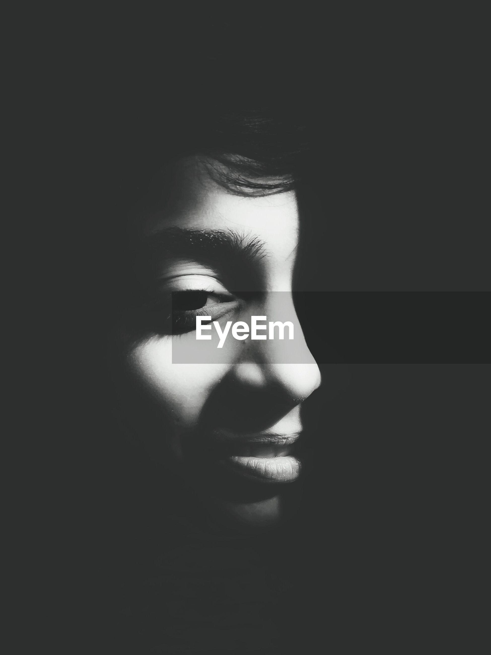 Close-up of boy against black background