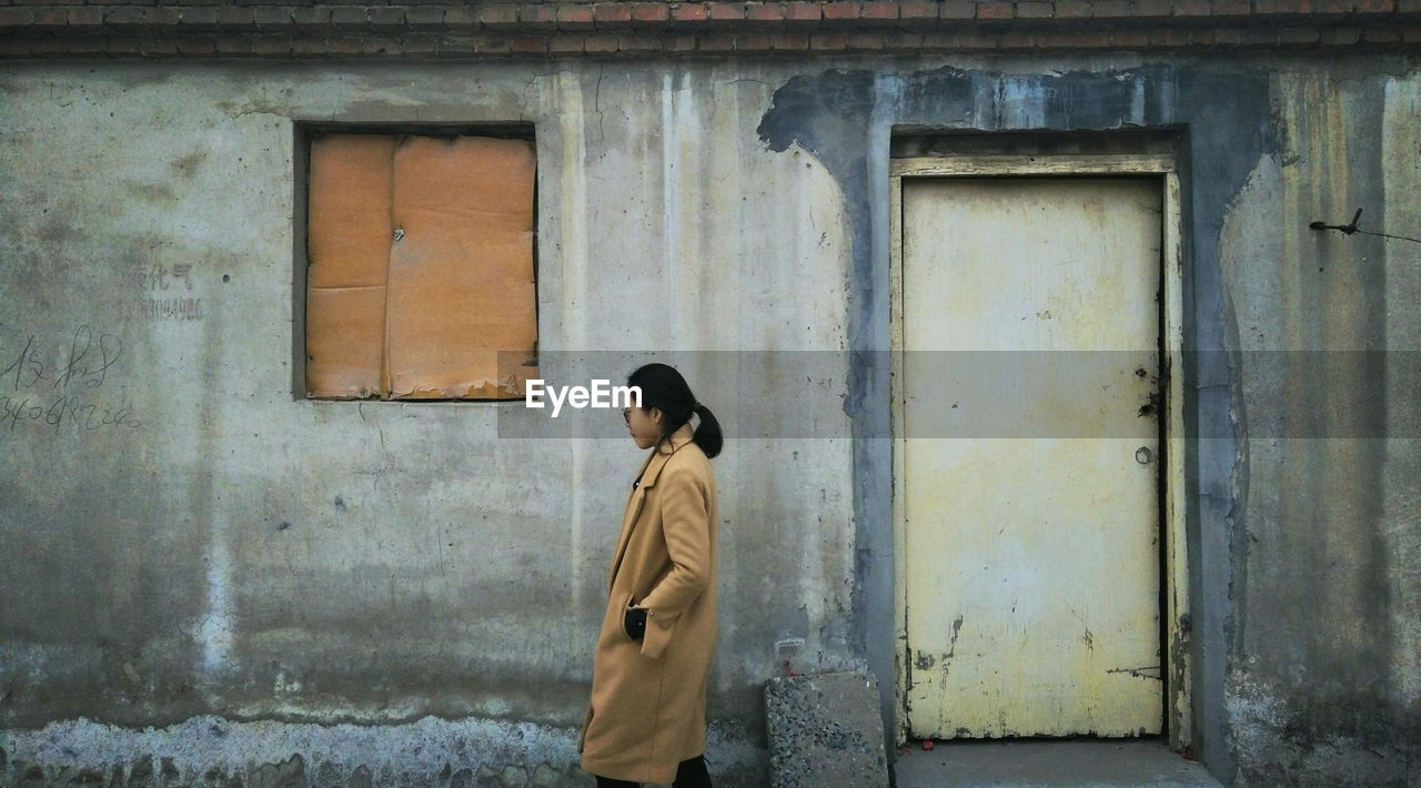 Side View Of Woman Walking By House