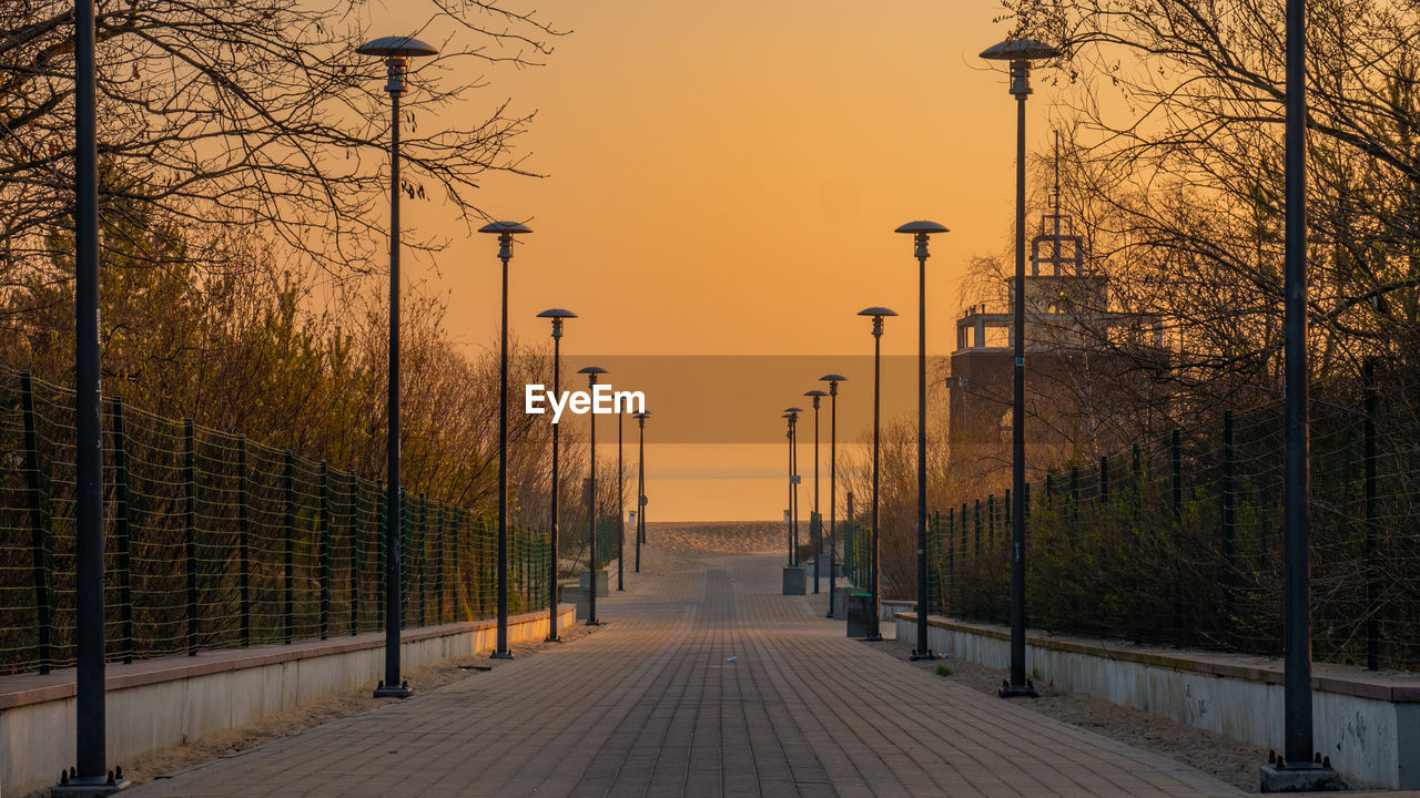 direction, the way forward, sunset, architecture, diminishing perspective, sky, tree, built structure, plant, street light, lighting equipment, no people, nature, footpath, street, railing, outdoors, bare tree, building exterior, orange color