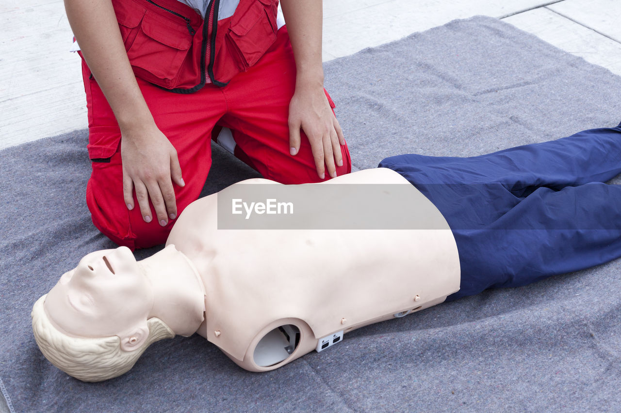 Low section of paramedic with cpr dummy on blanket