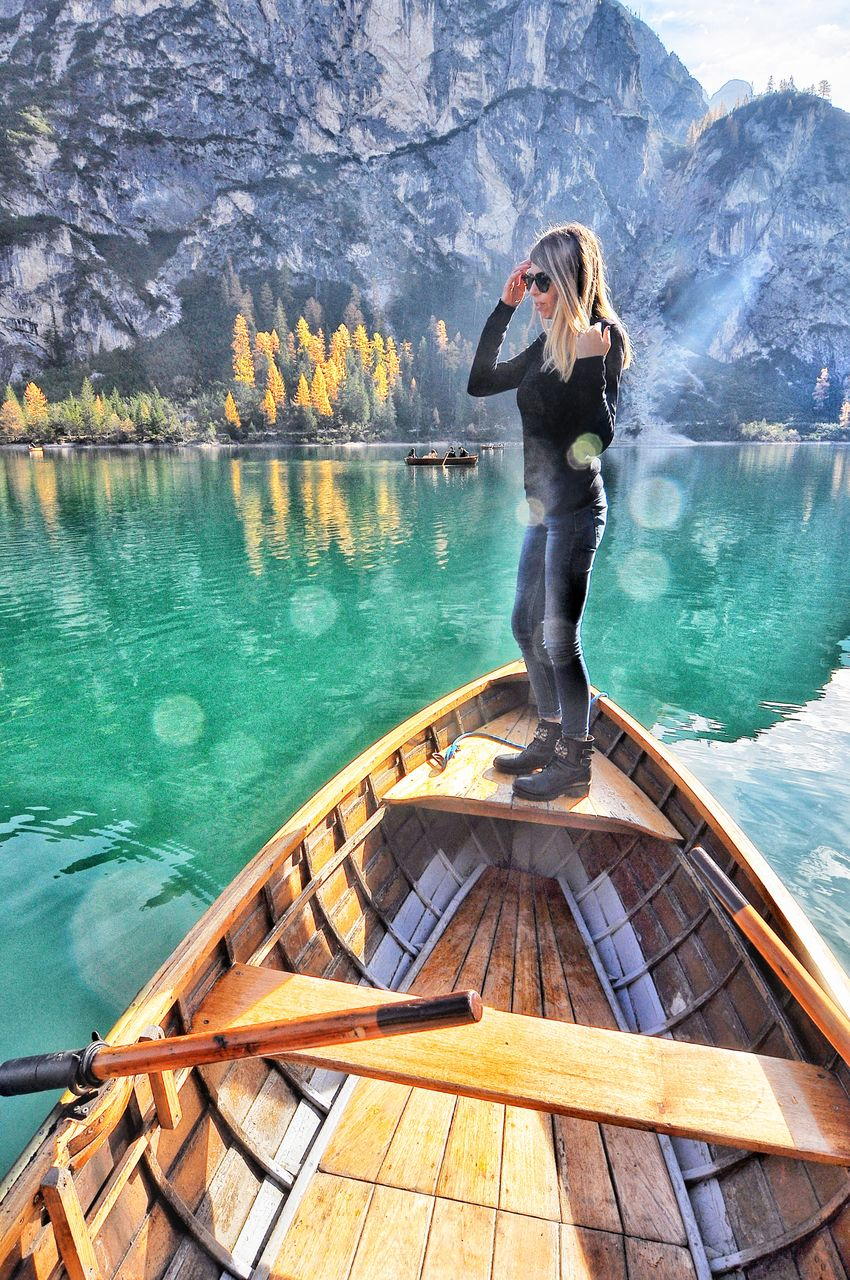 Full length of woman standing in boat on lake against mountains