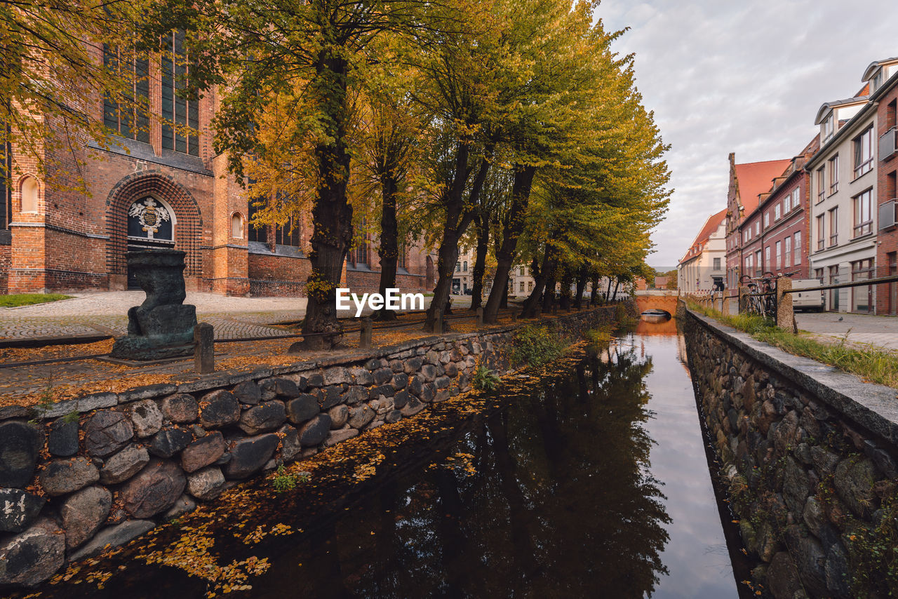 architecture, built structure, building exterior, water, tree, autumn, day, reflection, outdoors, no people, sky, residential building, nature, city