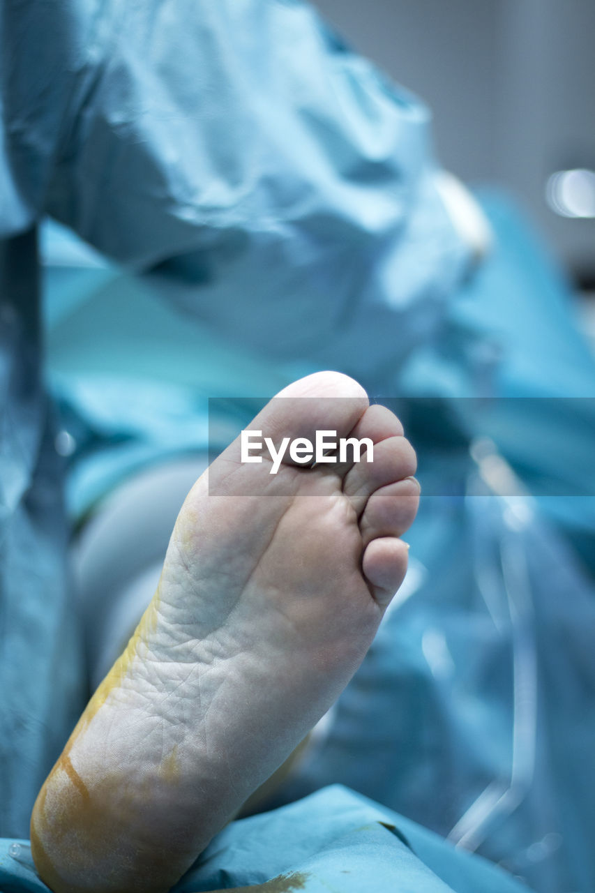 human hand, hand, human body part, close-up, body part, indoors, people, real people, bed, focus on foreground, hospital, human foot, healthcare and medicine, human leg, barefoot, limb, furniture, patient, low section, human limb, finger, care, surgical glove