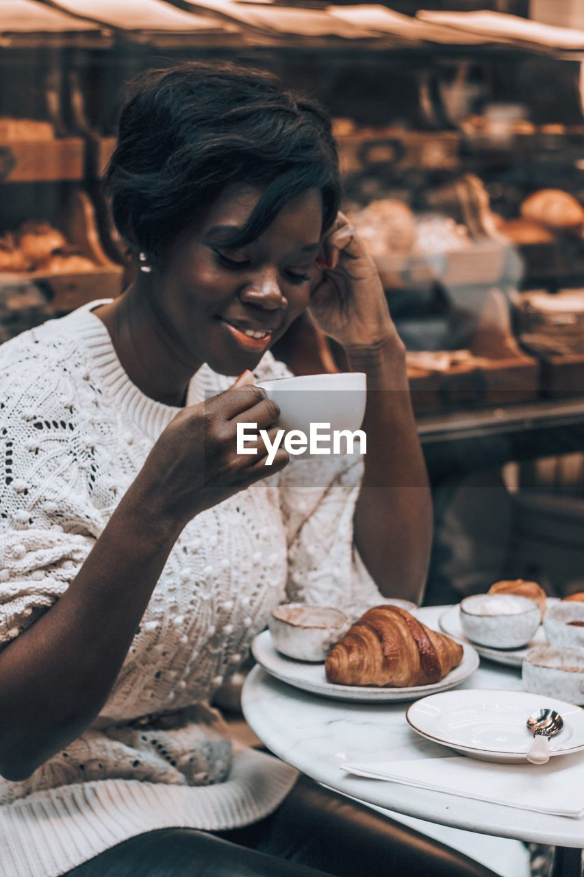 Woman Having Breakfast At Cafe