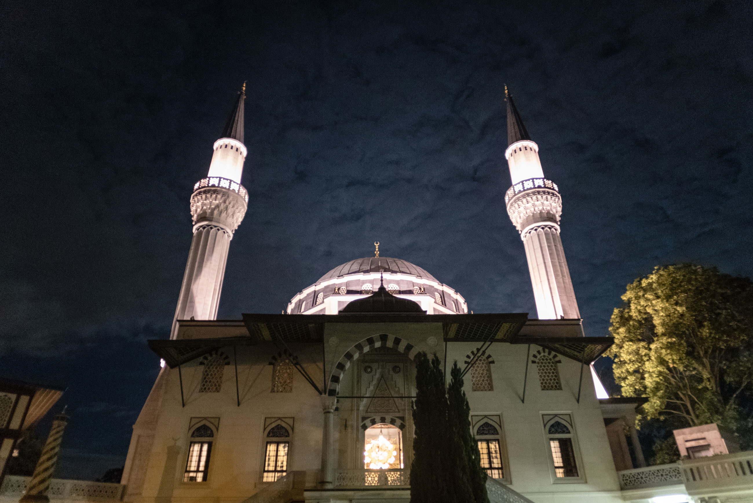 Low angle view of illuminated mosque against sky at night