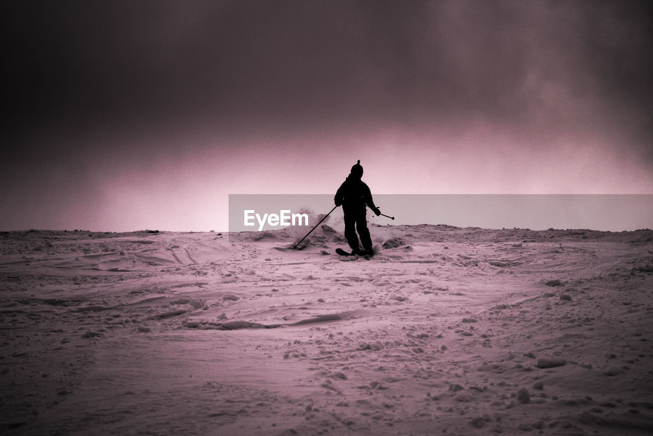 Rear View Of Silhouette Man Skiing On Snow Covered Field Against Sky