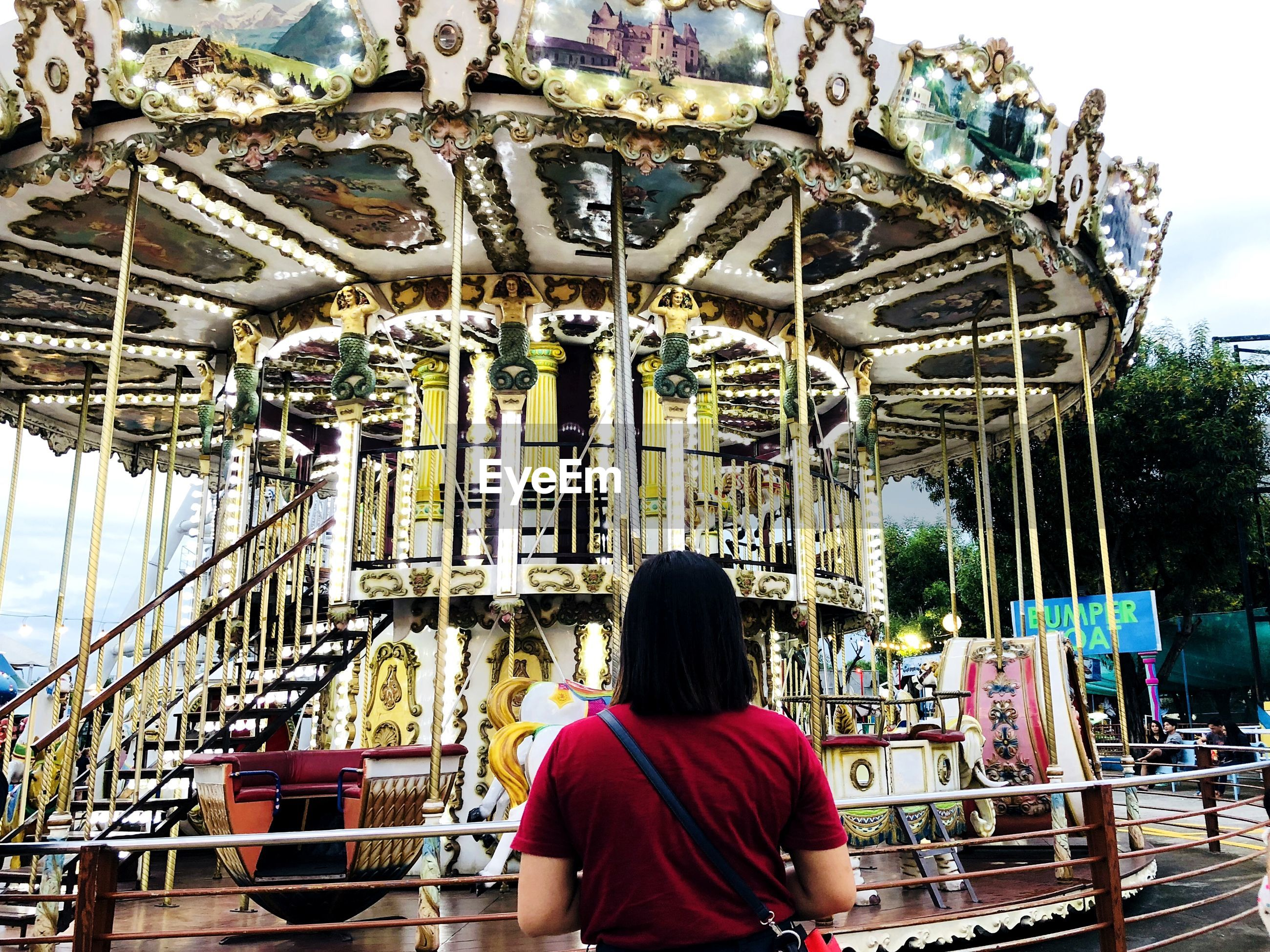 REAR VIEW OF WOMAN SITTING ON AMUSEMENT PARK RIDE