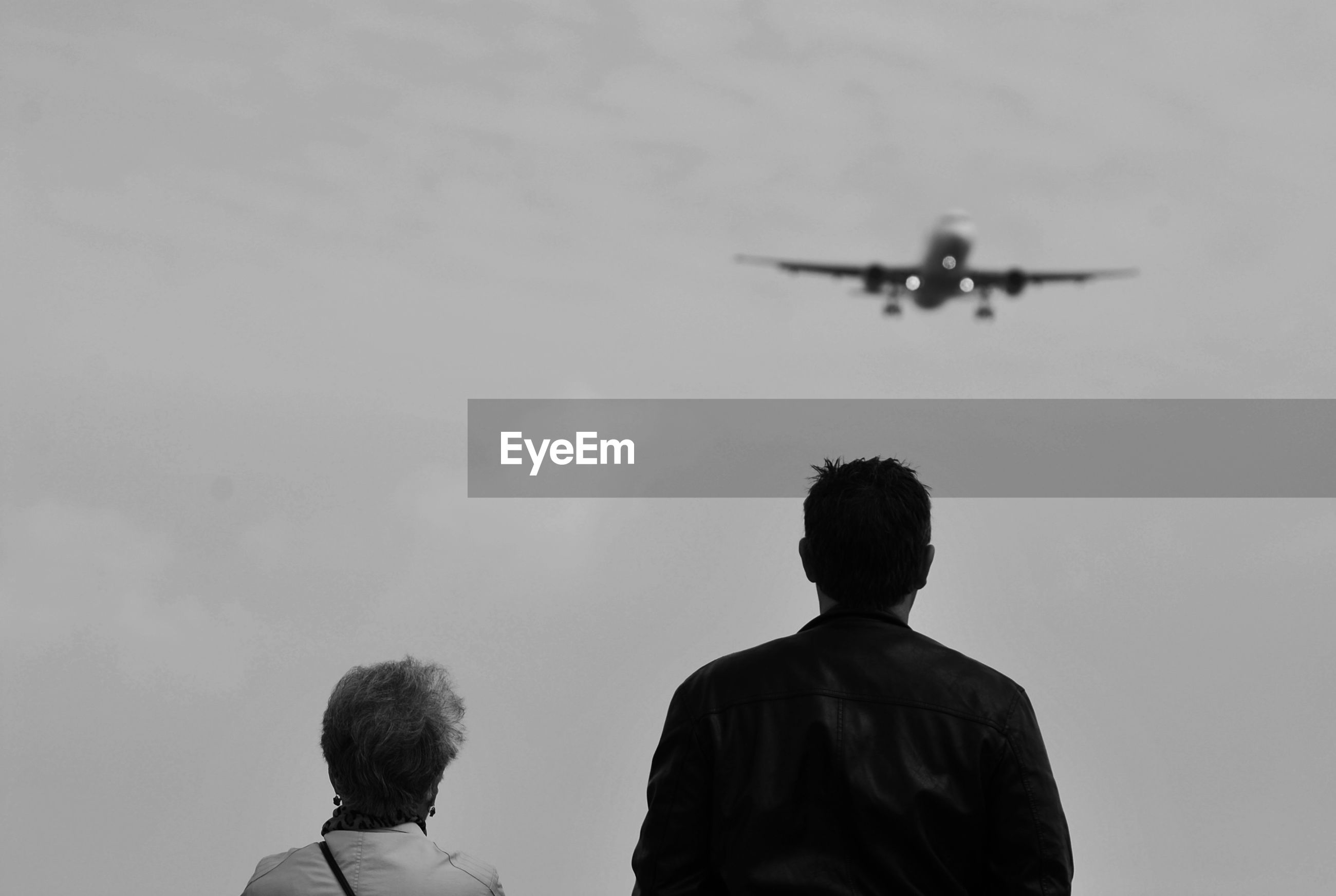 Low angle view of tourists watching airplane in sky