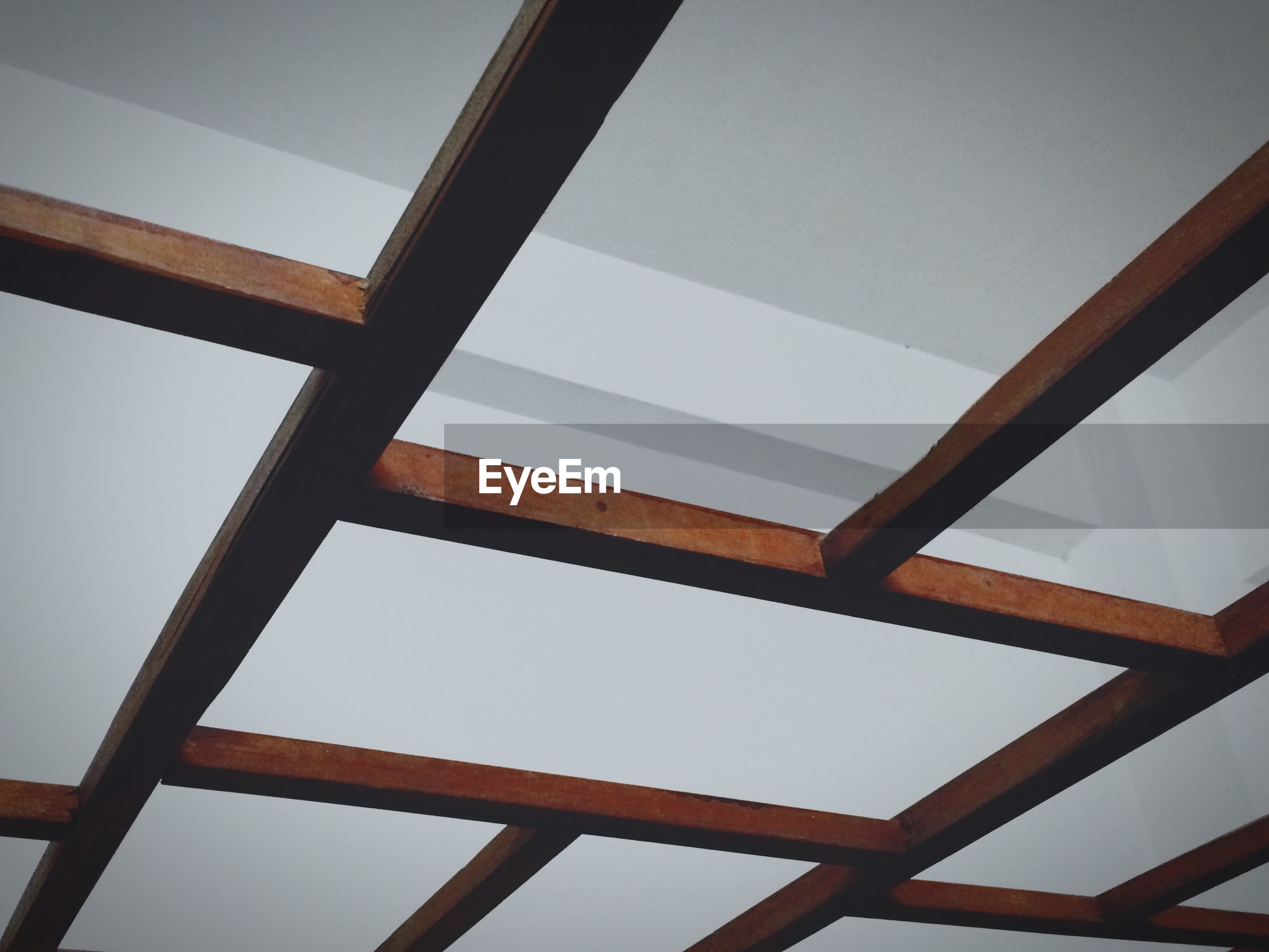 low angle view, clear sky, indoors, built structure, directly below, ceiling, metal, part of, architecture, sky, day, pattern, no people, metallic, geometric shape, cropped, copy space, close-up, window, wood - material