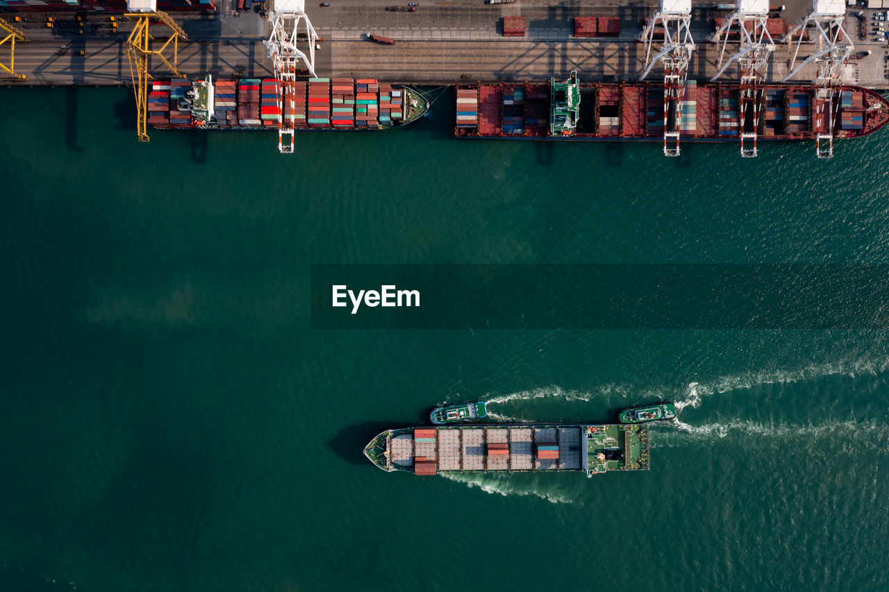 Aerial top view of containers ship floating in sea at shipping port for international import export