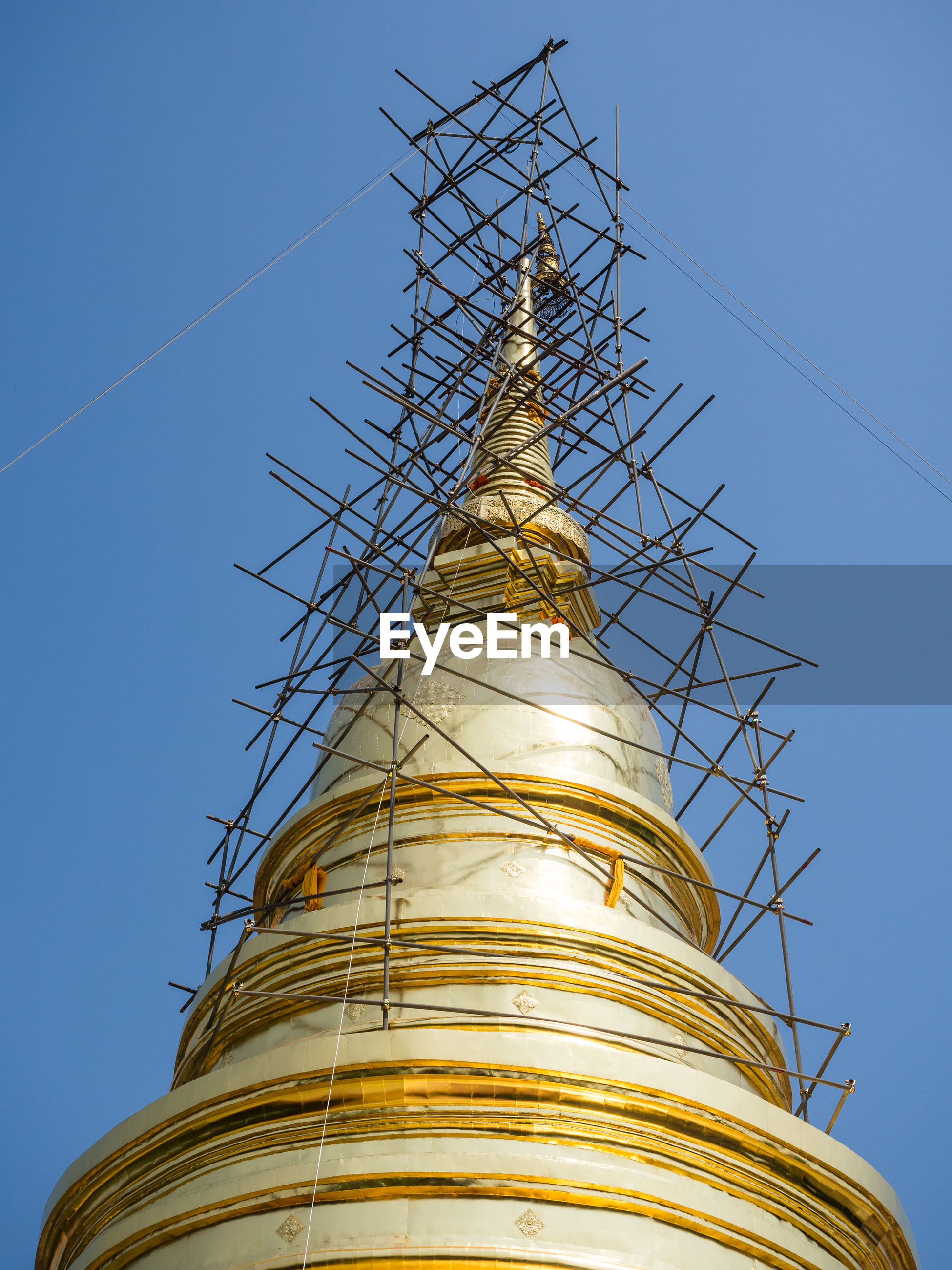 Low angle view of golden dome of buddhist temple wat phra singh with scaffolding, chiang mai, thailand