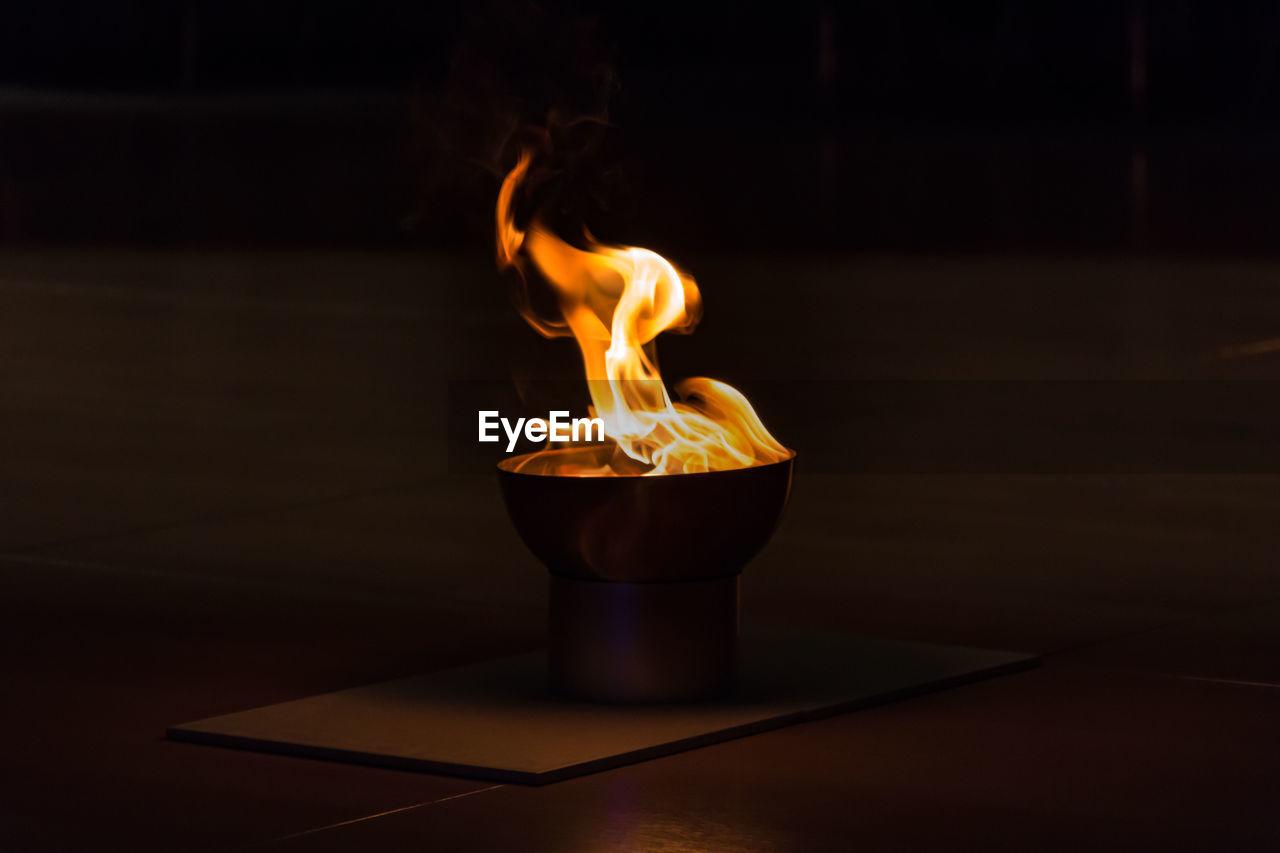 Close-Up Of Diya On Table In Darkroom