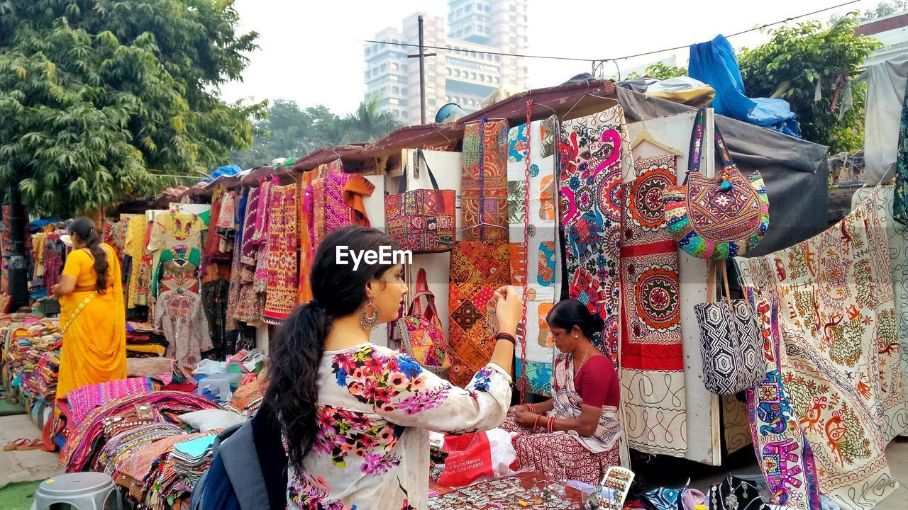 Young woman looking at earring while standing at market stall