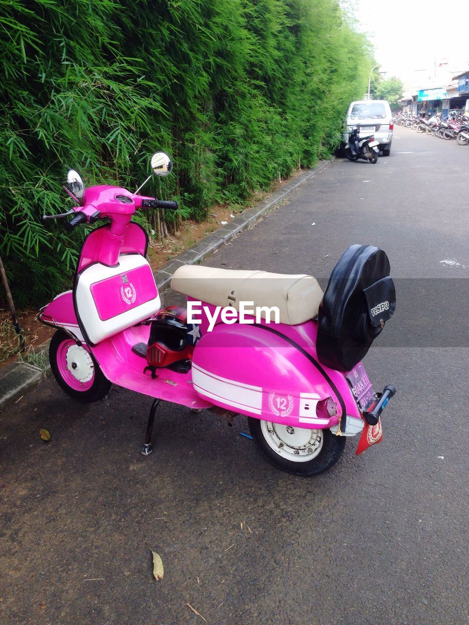 transportation, land vehicle, mode of transport, car, pink color, street, road, scooter, stationary, motorcycle, day, outdoors, toy car, tree, no people, sky