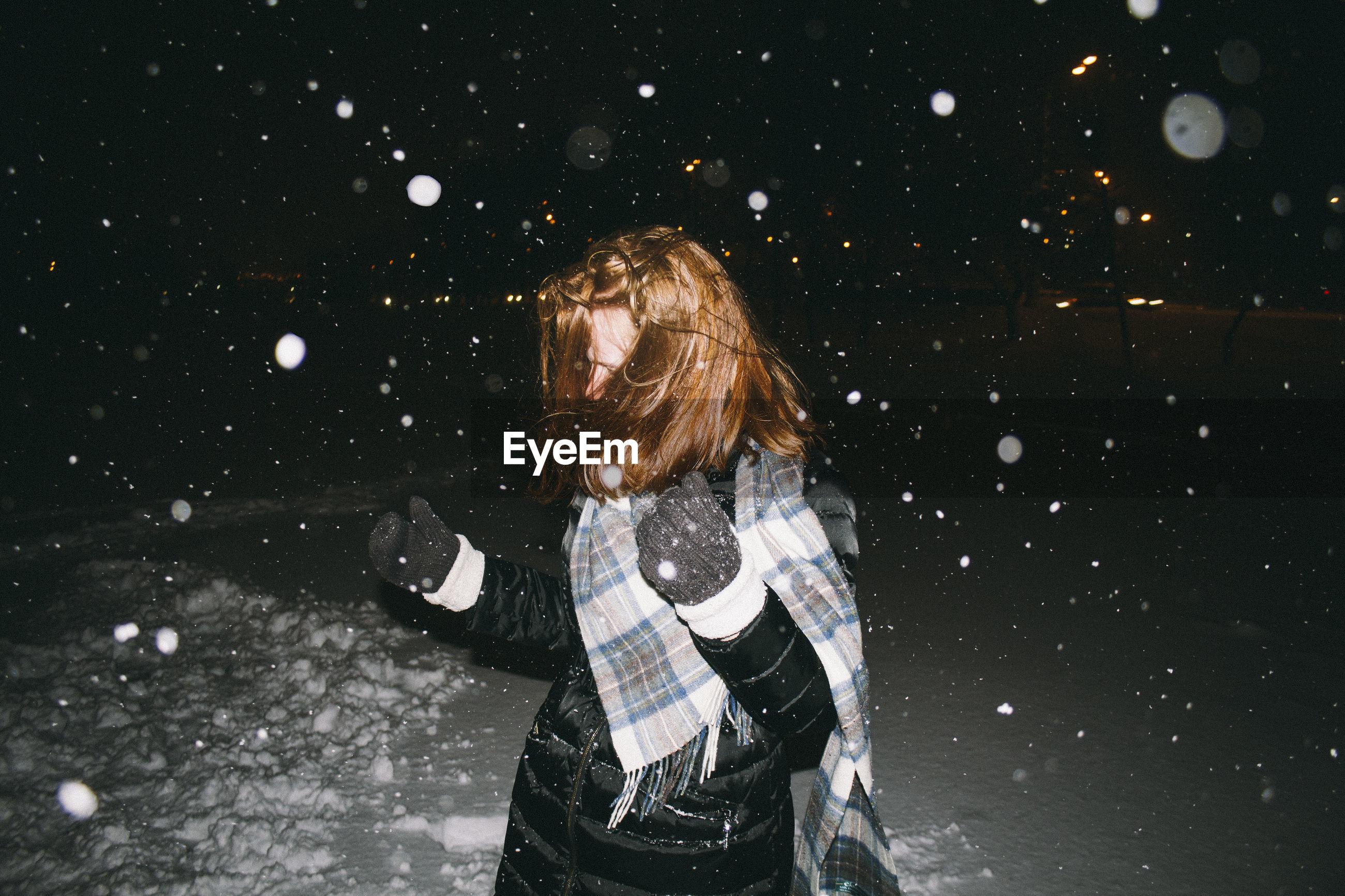 Playful woman during snowfall at night