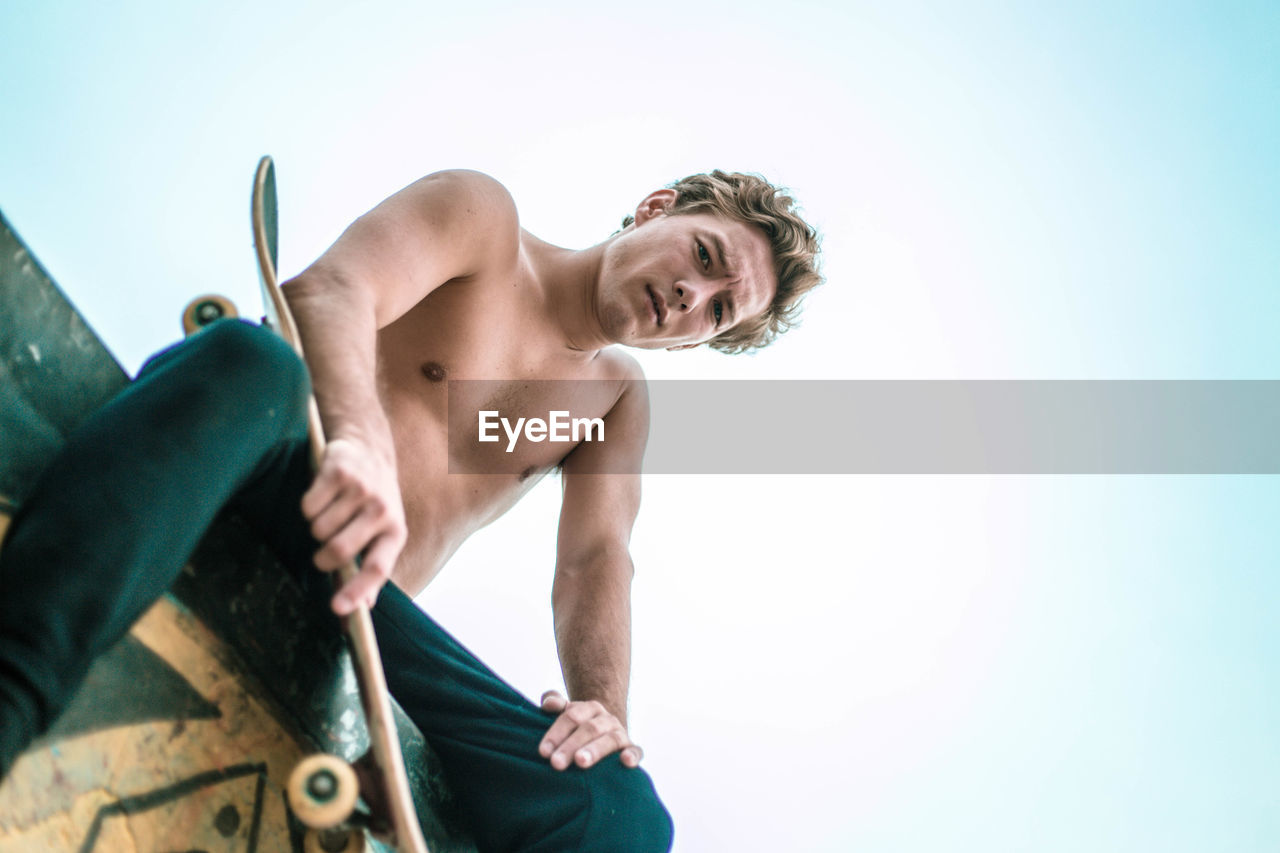 shirtless, one person, leisure activity, sky, lifestyles, day, copy space, clear sky, low angle view, holding, men, young adult, real people, standing, adult, three quarter length, nature, front view, outdoors