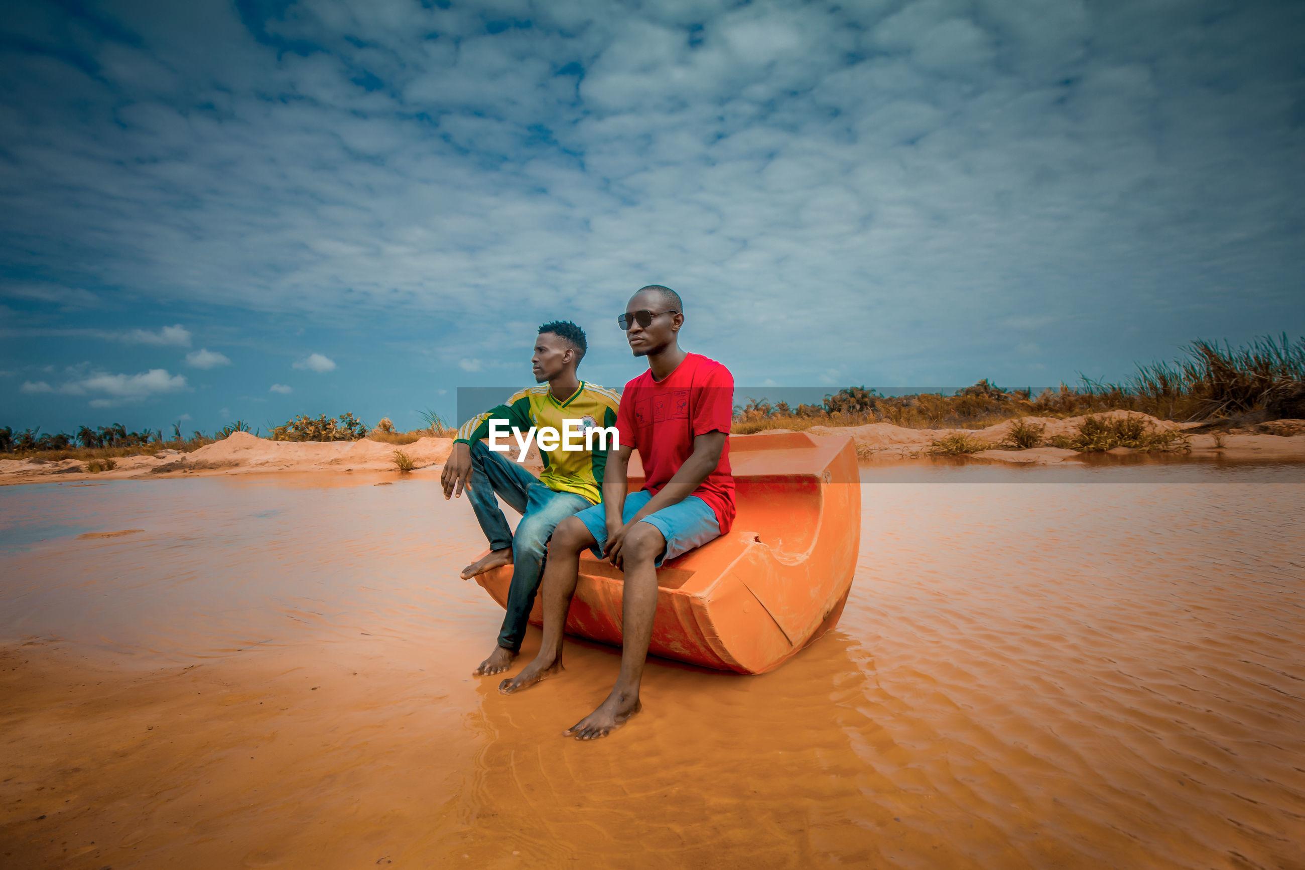 PORTRAIT OF MEN SITTING IN WATER AGAINST SKY