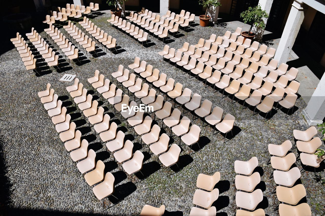 High Angle View Of Empty Chairs Arranged In Courtyard