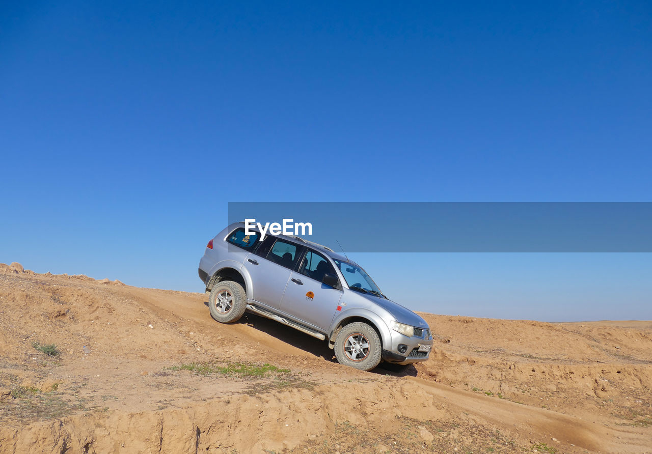 sky, clear sky, copy space, blue, land vehicle, transportation, mode of transportation, desert, car, nature, motor vehicle, landscape, land, environment, day, travel, off-road vehicle, no people, arid climate, sand, climate