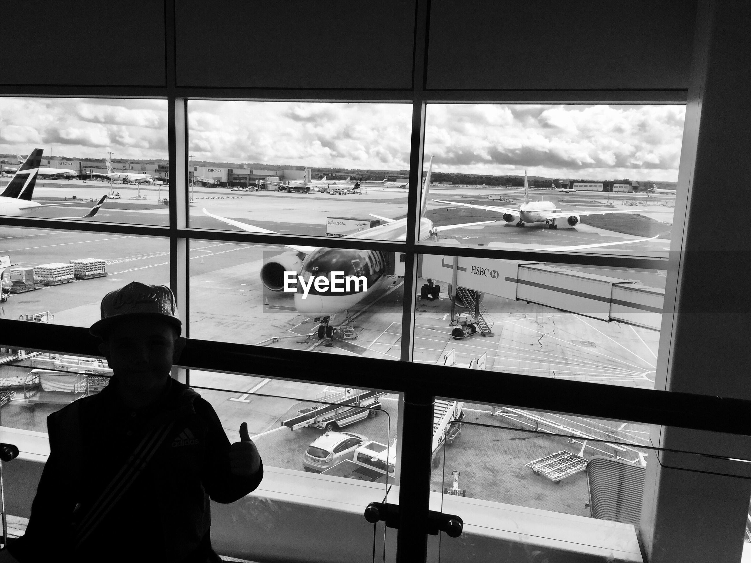 window, transportation, airport, travel, airplane, indoors, real people, mode of transport, looking through window, public transportation, sky, men, one person, day, standing, occupation, airport runway, window washer, people