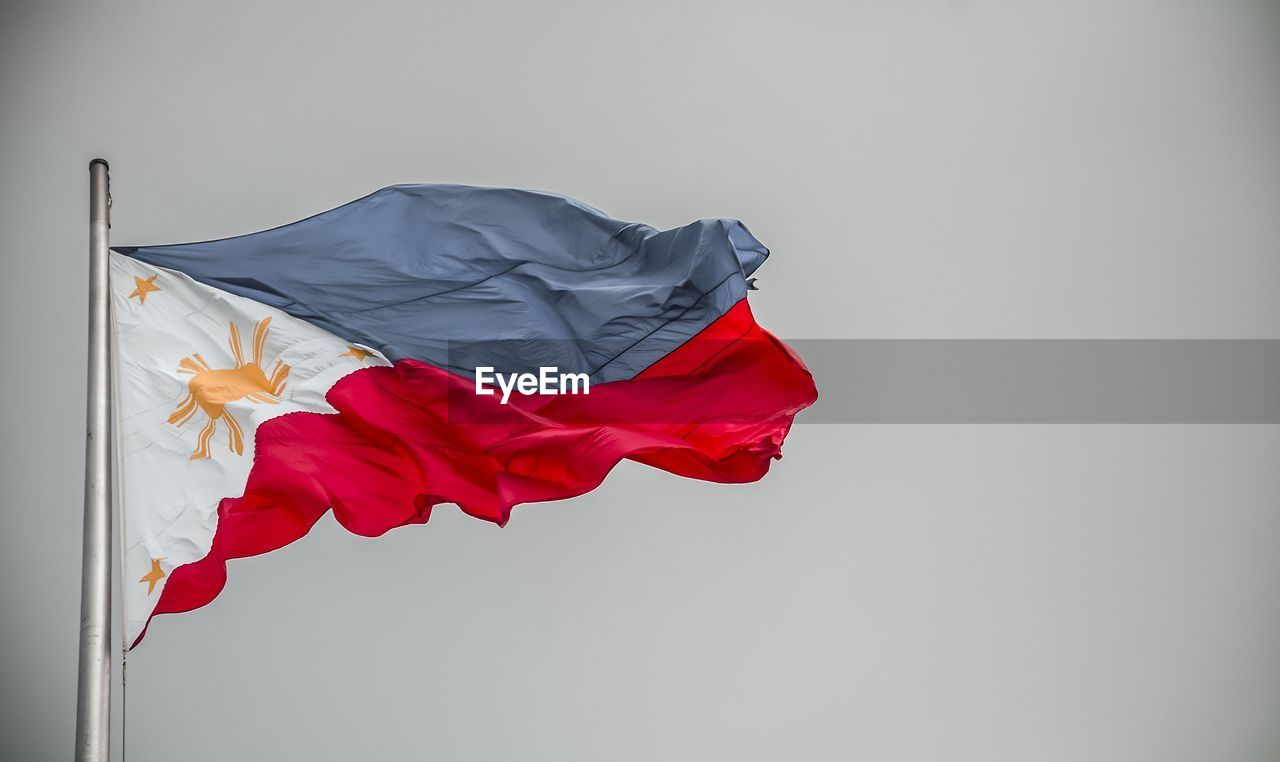 flag, patriotism, wind, copy space, red, environment, textile, waving, no people, day, nature, pole, pride, low angle view, sky, white background, studio shot, white color, clear sky, national icon