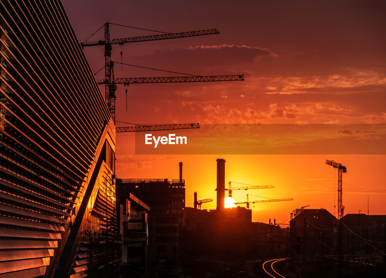 Silhouette Factory Against Orange Sky