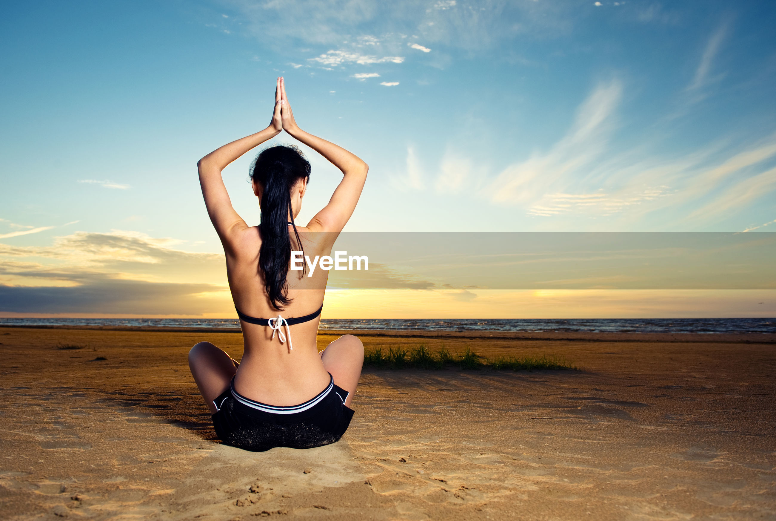 Woman practicing yoga at beach during sunset