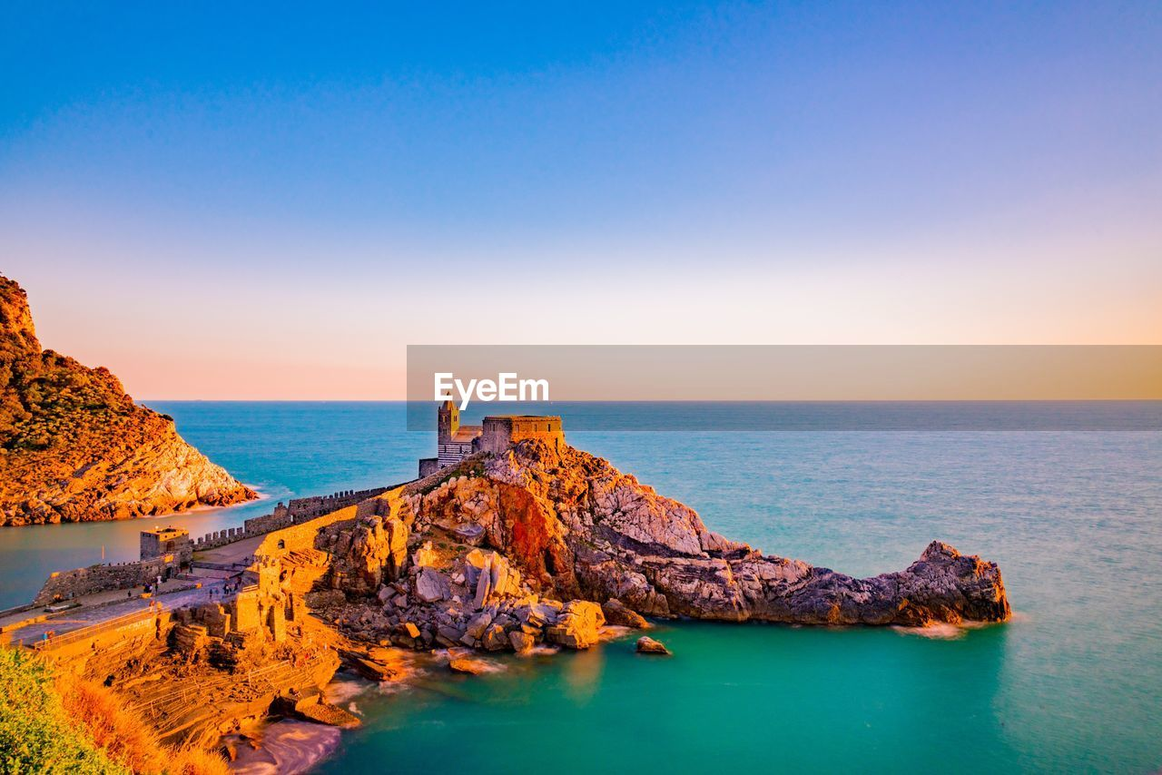 water, sky, sea, horizon over water, scenics - nature, horizon, beauty in nature, rock, rock - object, solid, tranquil scene, tranquility, nature, rock formation, blue, idyllic, land, copy space, clear sky, no people, outdoors, rocky coastline