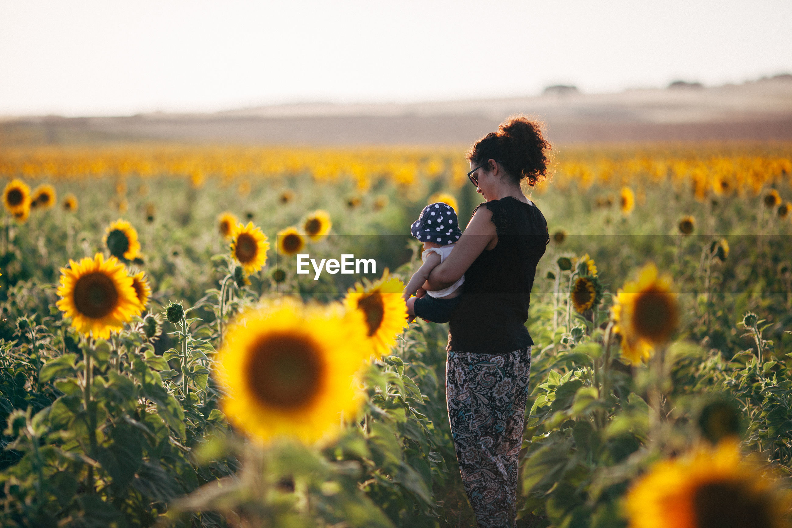 Side view of mother carrying daughter while standing amidst sunflowers in field against sky