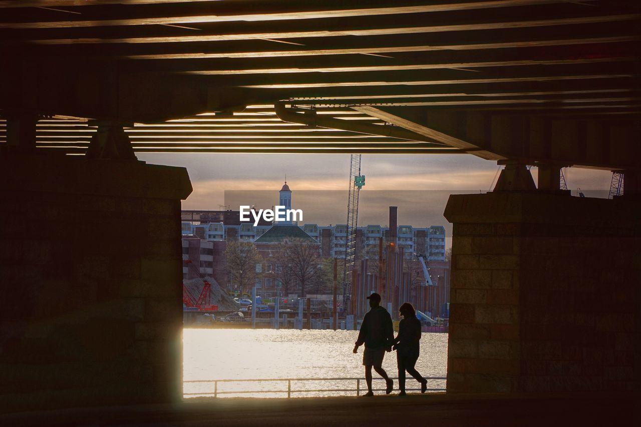 Couple Walking By River Below Bridge