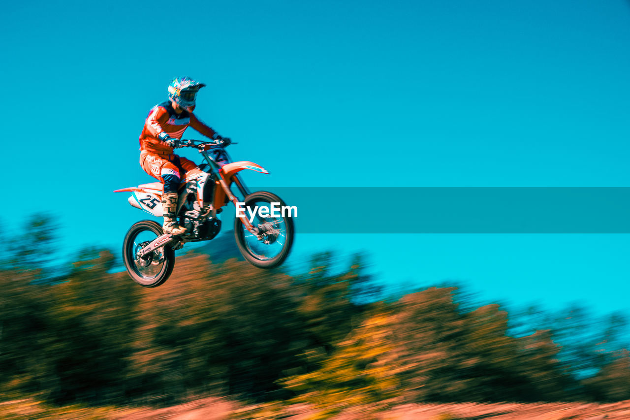 stunt, sport, skill, motion, helmet, headwear, transportation, mode of transportation, mid-air, real people, extreme sports, leisure activity, motorcycle, nature, riding, motocross, jumping, lifestyles, ride, one person, biker, outdoors, crash helmet
