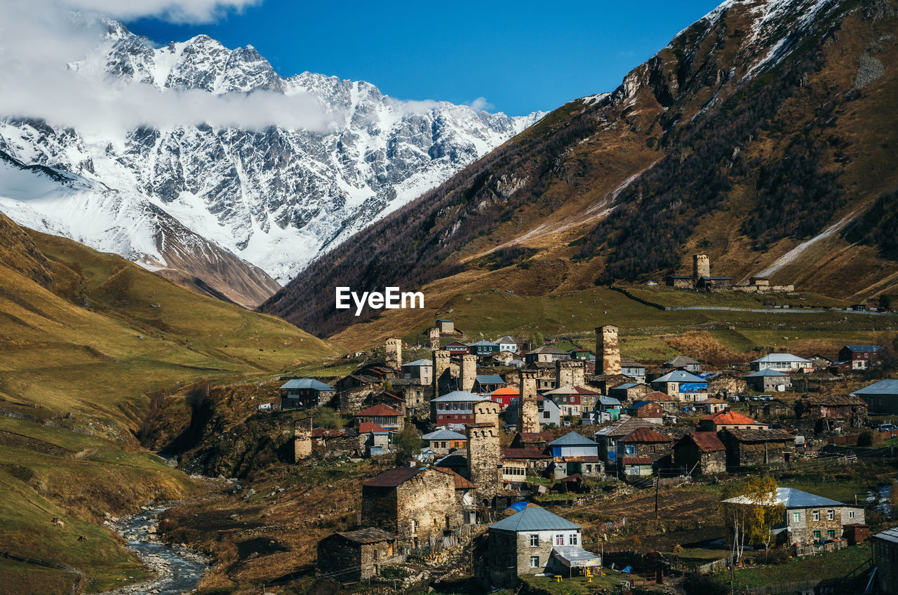Village By Snowcapped Mountains Against Sky