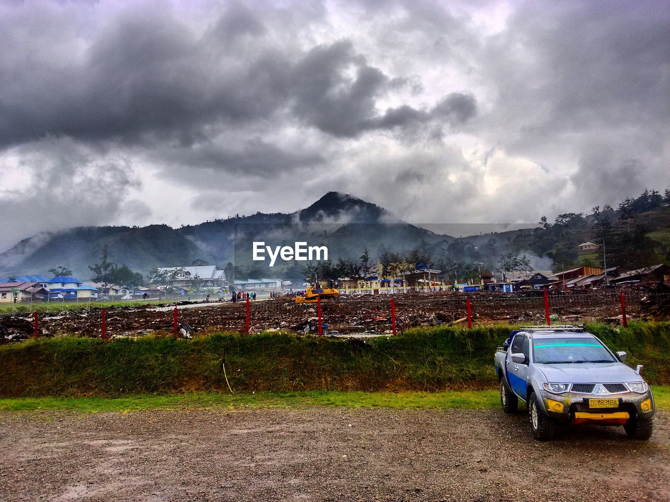CAR ON FIELD AGAINST MOUNTAINS