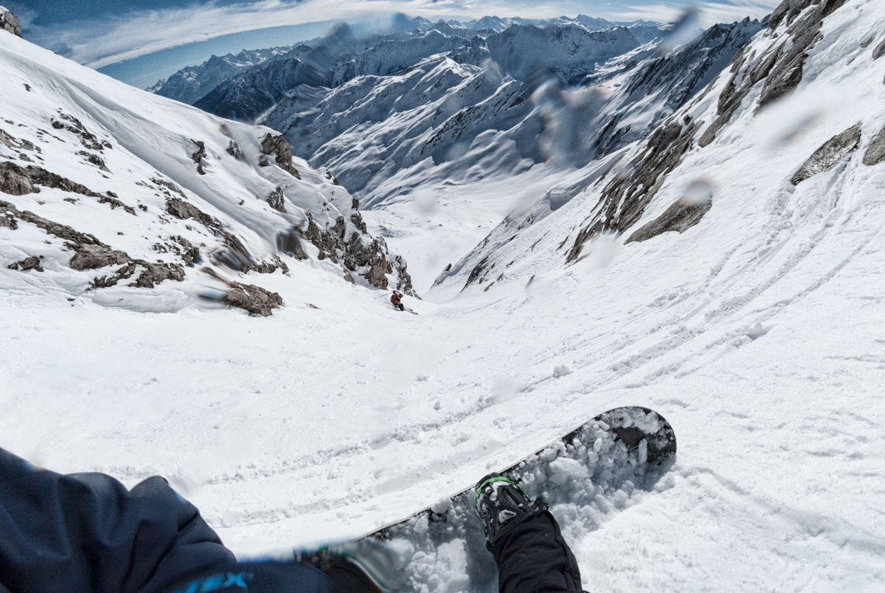 Low section of person snowboarding on mountain