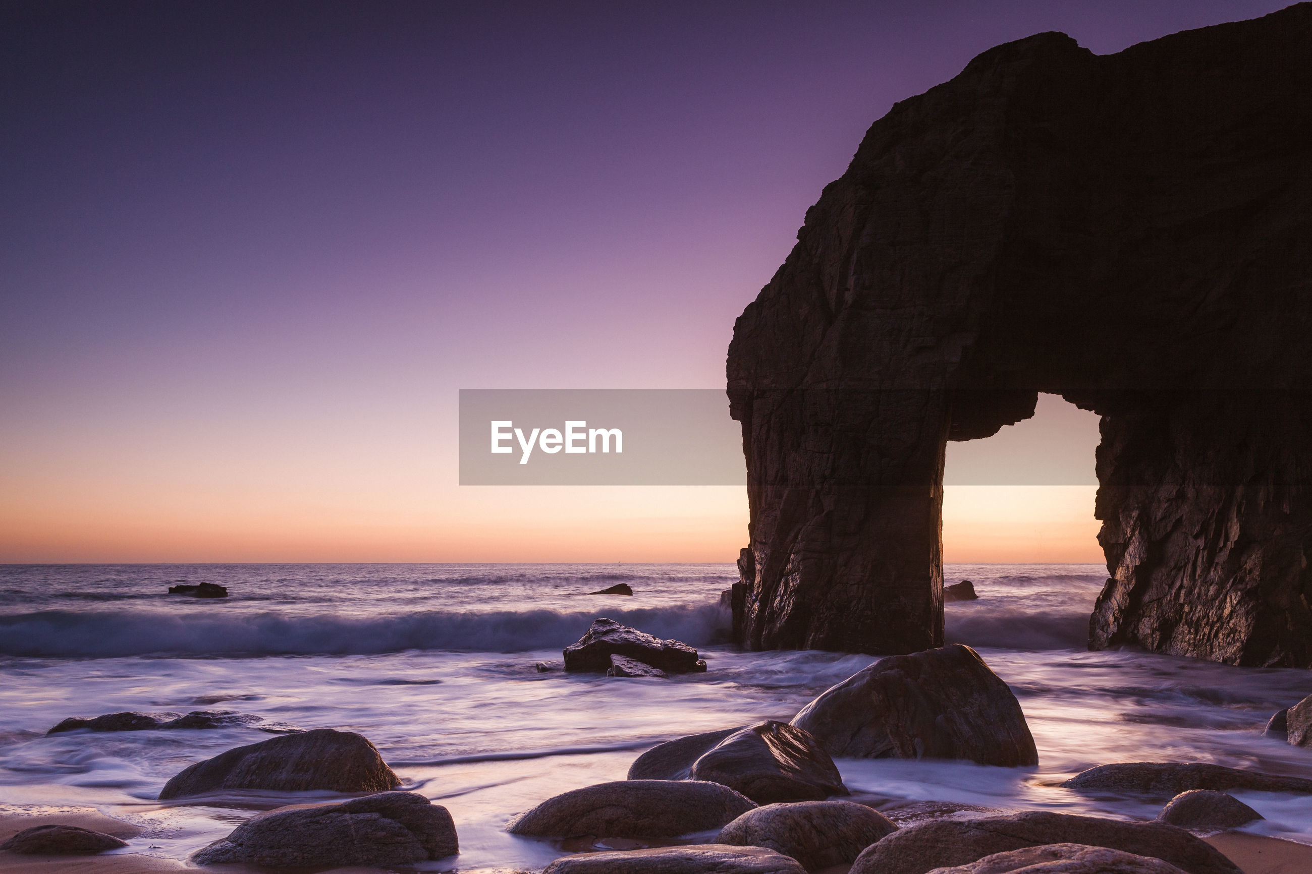 ROCK FORMATION AT BEACH AGAINST CLEAR SKY
