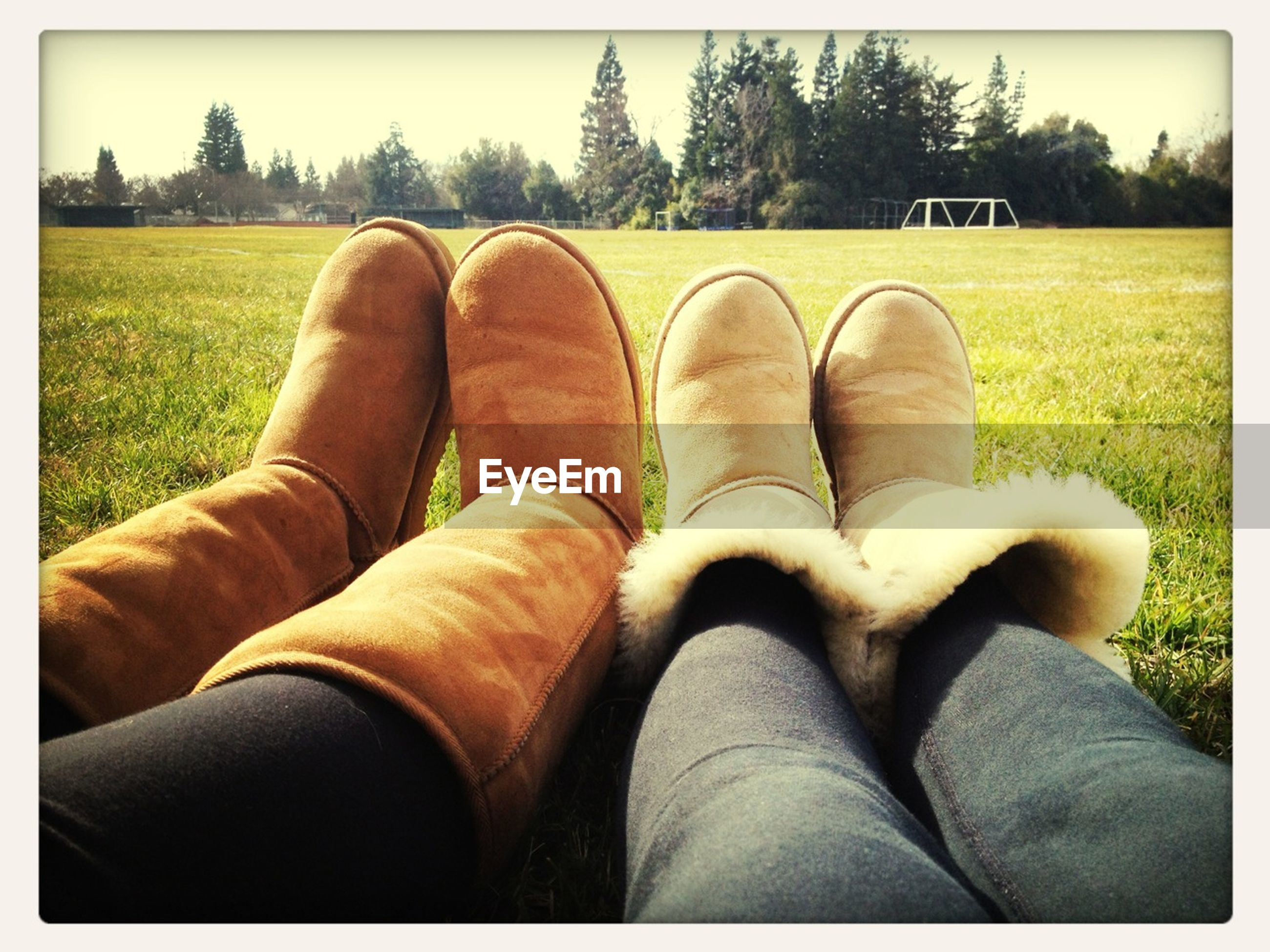 low section, person, shoe, transfer print, personal perspective, footwear, grass, human foot, auto post production filter, field, relaxation, jeans, lifestyles, leisure activity, sitting, grassy, togetherness