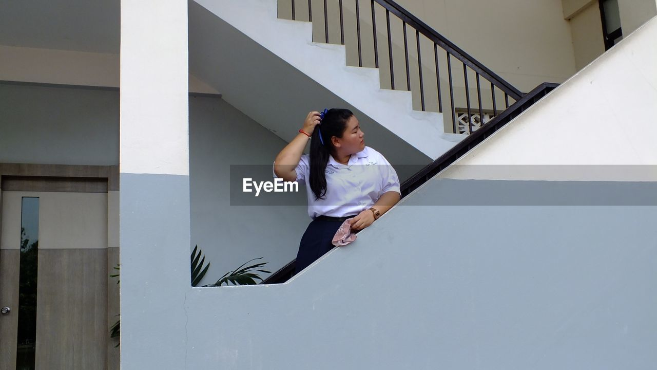 Teenage girl in school uniform standing on staircase of building
